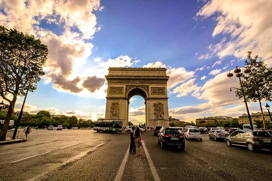 Arc de triomphe avec deux touristes, place de l'étoile sur le haut des champs elysées