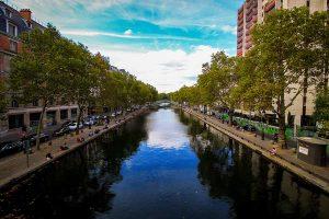 Canal Saint Martin bordé d'arbres fleuris avec ciel bleu se reflétant dans l'eau