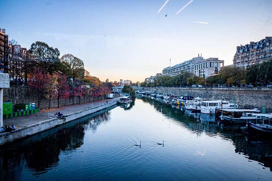 Port de l'arsenal vue depuis le métro Bastille sur la ligne 1, péniches, ciel bleu, fin de journée
