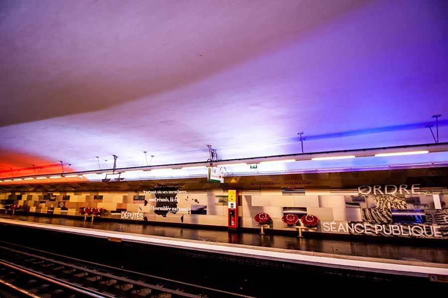 Station de Métro Assemblée Nationale avec ses lumières bleu blanc et rouge qui éclairent le plafond et les textes de lois sur les murs