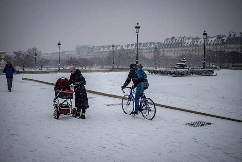 cycliste à vélo roulant sous la neige en hiver dans le jardin des tuileries a coté d'une femme et sa poussette