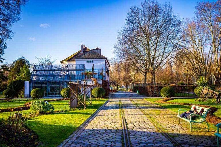Allée du Parc de Bercy avec anciens rails pour les marchandises, ciel bleu, fin d'après midi, hiver, arbres nus, bancs