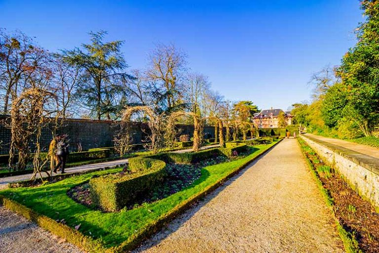 Allée fleurie dans le Parc de Bagatelle dans le bois de Boulogne avec ciel bleu en hiver