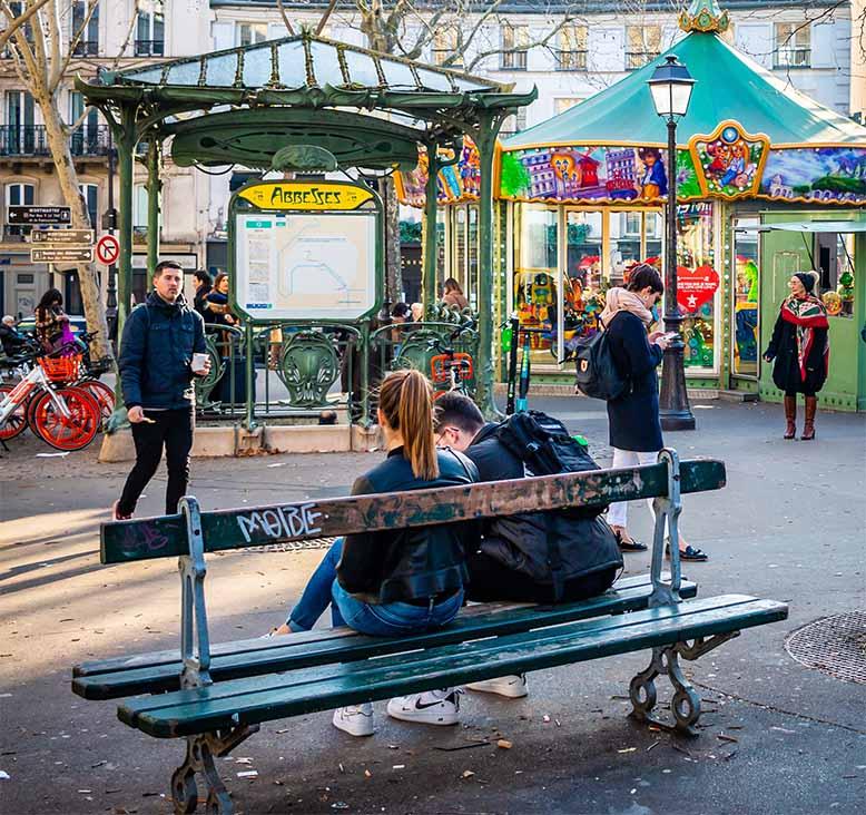 Abbesses couple assis sur banc devant sortie métro