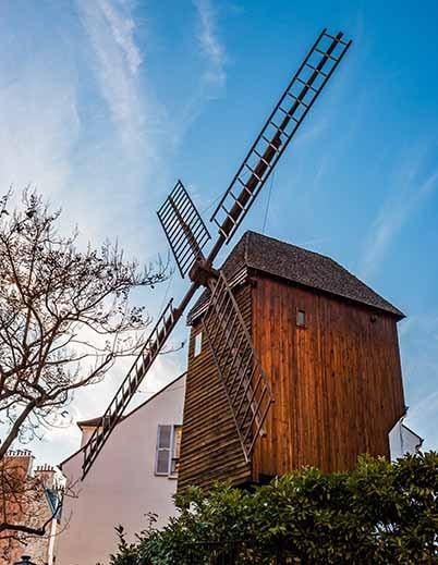 Butte Montmartre Le moulin de la Galette sur fond ciel bleu