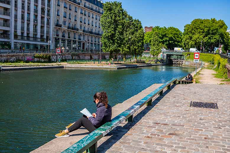 Canal Saint-Martin femme assise en train de lire quai de Jemmapes printemps