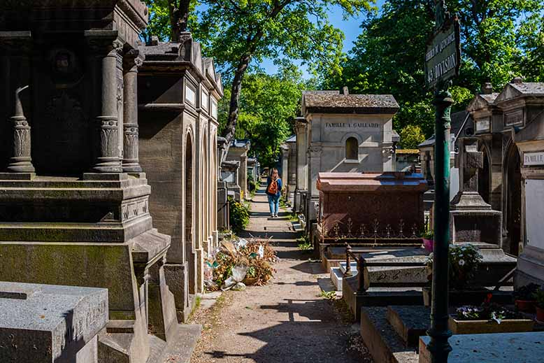 Cimetière du Père Lachaise allée petite bordée avec des tombes au soleil femme au loin