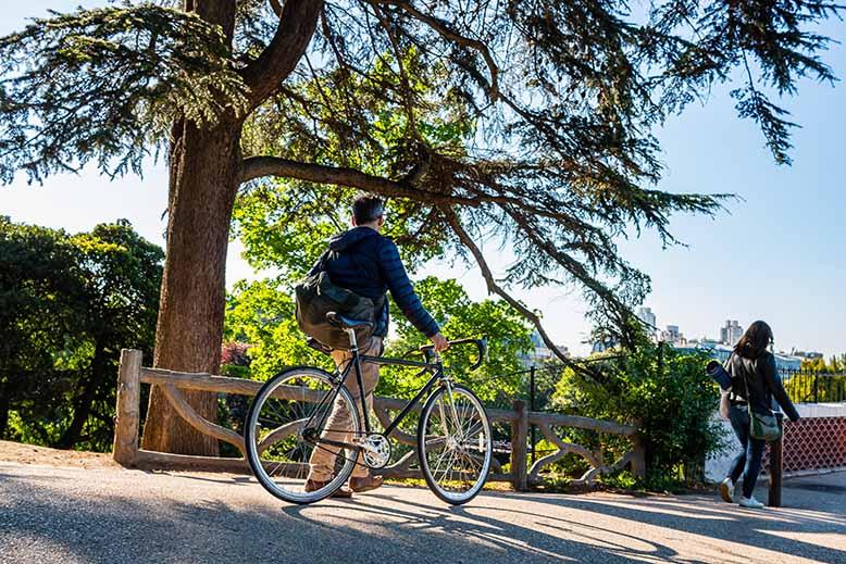 Parc des Buttes Chaumont homme tenant son vélo dans la main vers le temple de la Sibylle