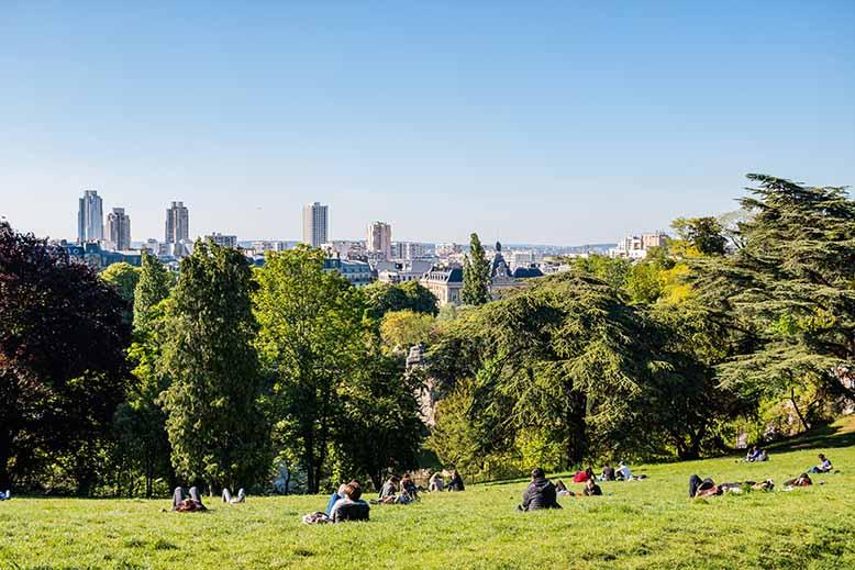 Parc des Buttes Chaumont scène de vie personnes allongées dans l'herbe en fin d'après-midi