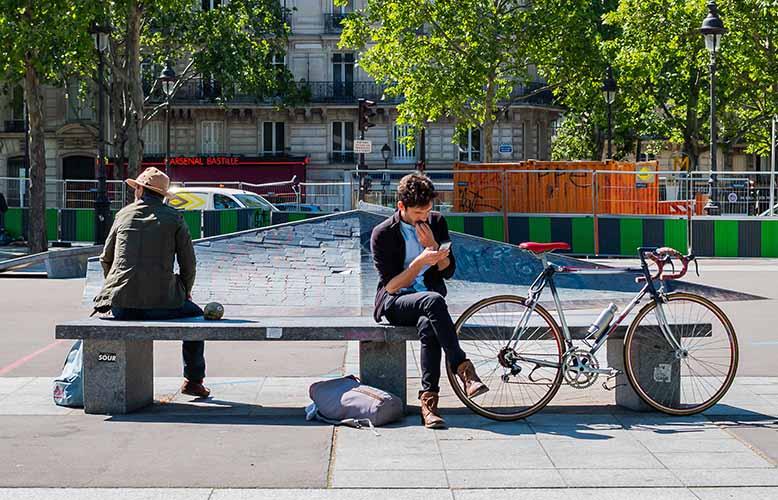 Place de la Bastille plan rapproché sur scène de vie hommes assis sur un banc