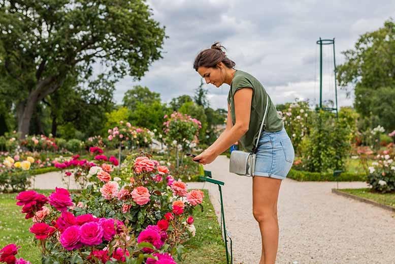 Visiter le Bois de Boulogne femme prenant une photo dans le parc de Bagatelle