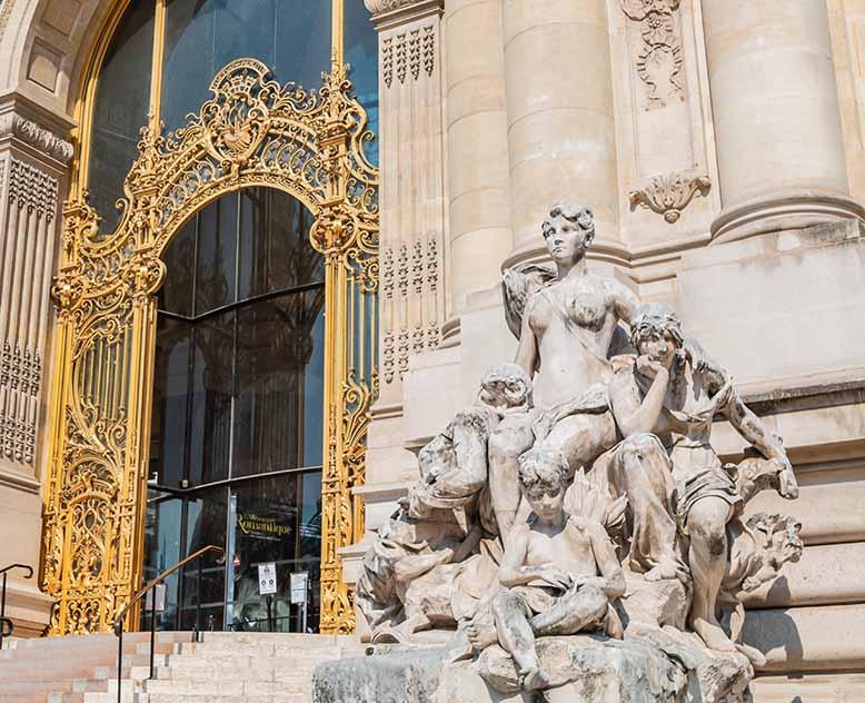 Visiter le Petit Palais entrée marquée par la grille et la statue de la Seine et ses affluents