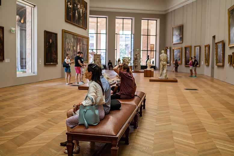 Visiter le Petit Palais visiteurs assis face à une des grandes oeuvres